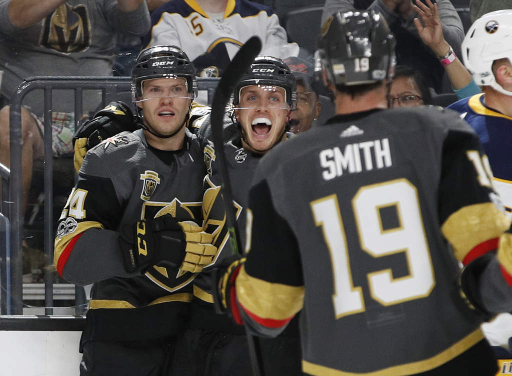 Vegas Golden Knights defenseman Nate Schmidt, right, celebrates with Vegas Golden Knights center Oscar Lindberg after Lindberg scored against the Buffalo Sabres during the first period of an NHL hockey game Tuesday, Oct. 17, 2017, in Las Vegas. (AP Photo/John Locher)